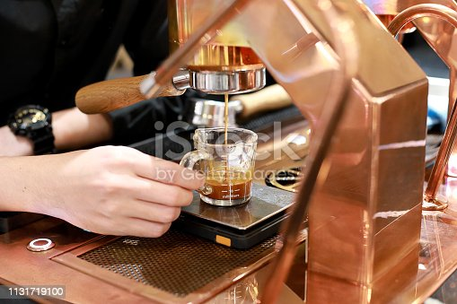 istock Hand of Barista making coffee with the coffee machine in the coffee shop or cafe, Foods and drink concept. Warm Tone. 1131719100