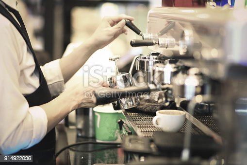 istock Hand of Barista making coffee with the coffee machine in the coffee shop or cafe, Foods and drink concept. Warm Tone. 914922036