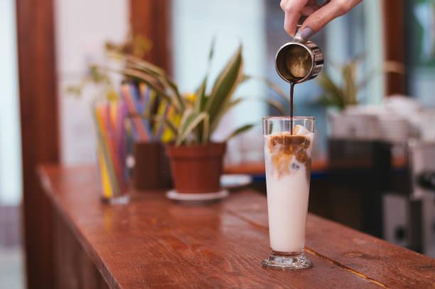 hand des barista latte oder cappuccino kaffee milch gießen - schokolikör stock-fotos und bilder