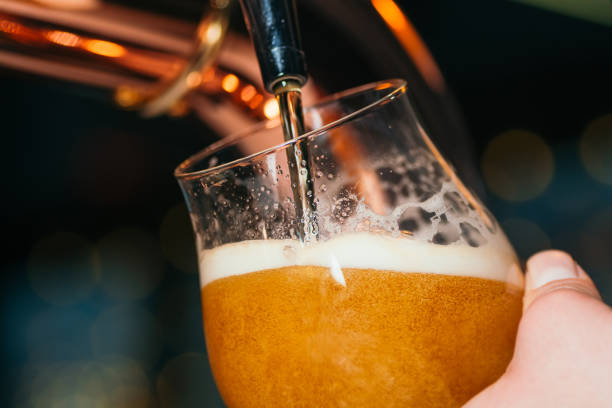 Hand of bartender pouring a lager beer in tap close up stock photo