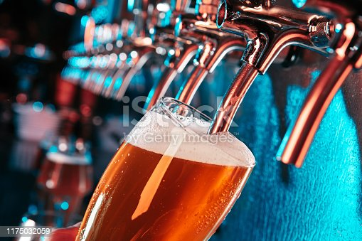 Hand of bartender pouring a large lager beer in tap. Bright and modern neon light, males hands. Pouring beer for client. Side view of young bartender pouring beer while standing at the bar counter.