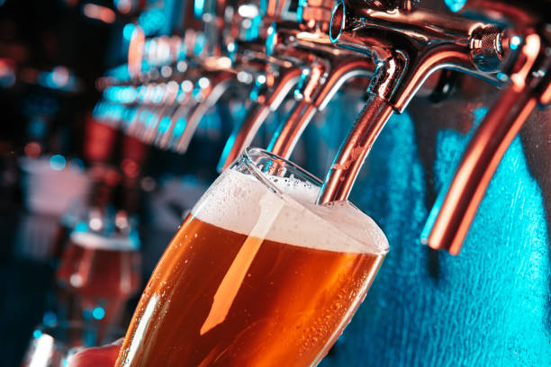 Hand of bartender pouring a large lager beer in tap stock photo