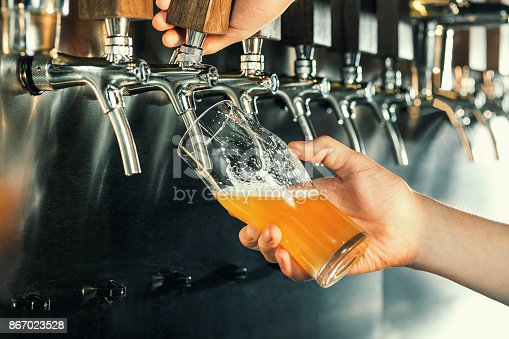 istock Hand of bartender pouring a large lager beer in tap 867023528