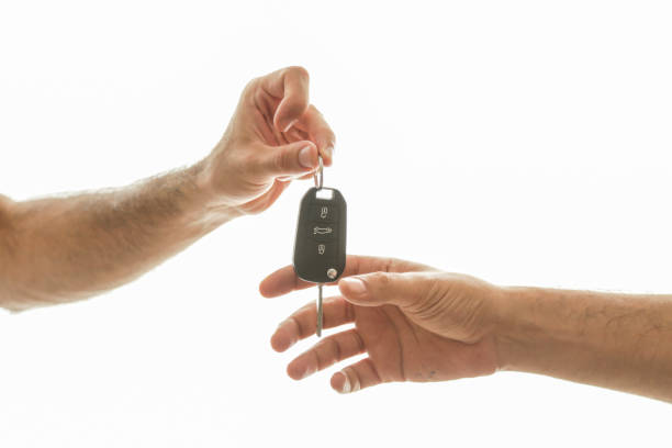 Hand of business man gives the car key with isolated on white stock photo