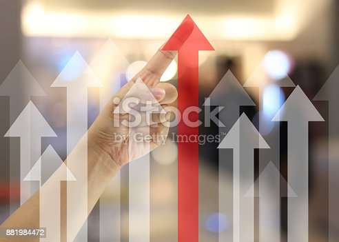 Hand of business man point to the highest point of the red arrow in concept of targeted and profitable in presentation.