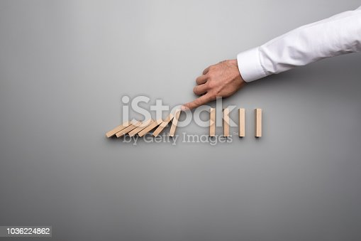 Hand of business man stopping falling domino pieces. Includes copy space over gray table.