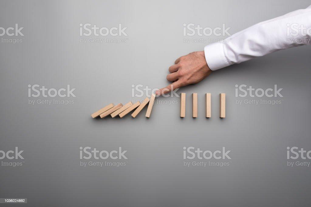 Hand des Geschäfts Mann stoppen fallende Dominosteine – Foto