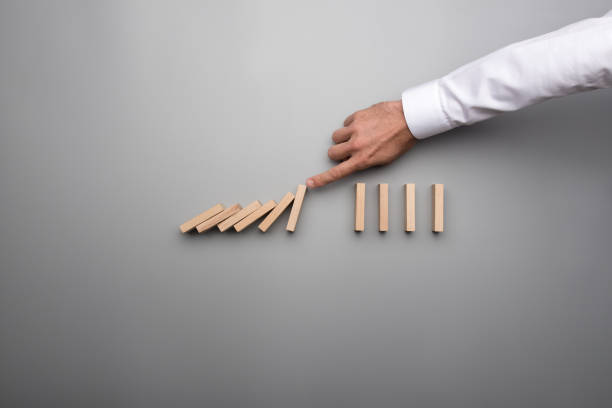 Hand of business man stopping falling domino pieces stock photo
