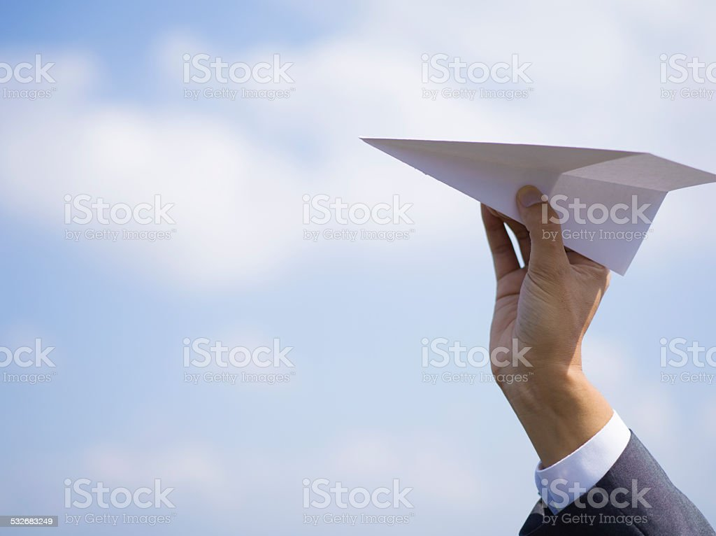 Hand of business man with a paper airplane stock photo