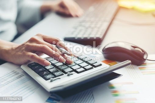 Close up hand of business woman accountant or banker making calculations. Savings, finances and economy audit debt concept
