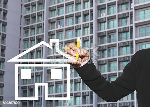 875531516istockphoto hand of business woman using yellow pen write symbol of house on glass window 899367800