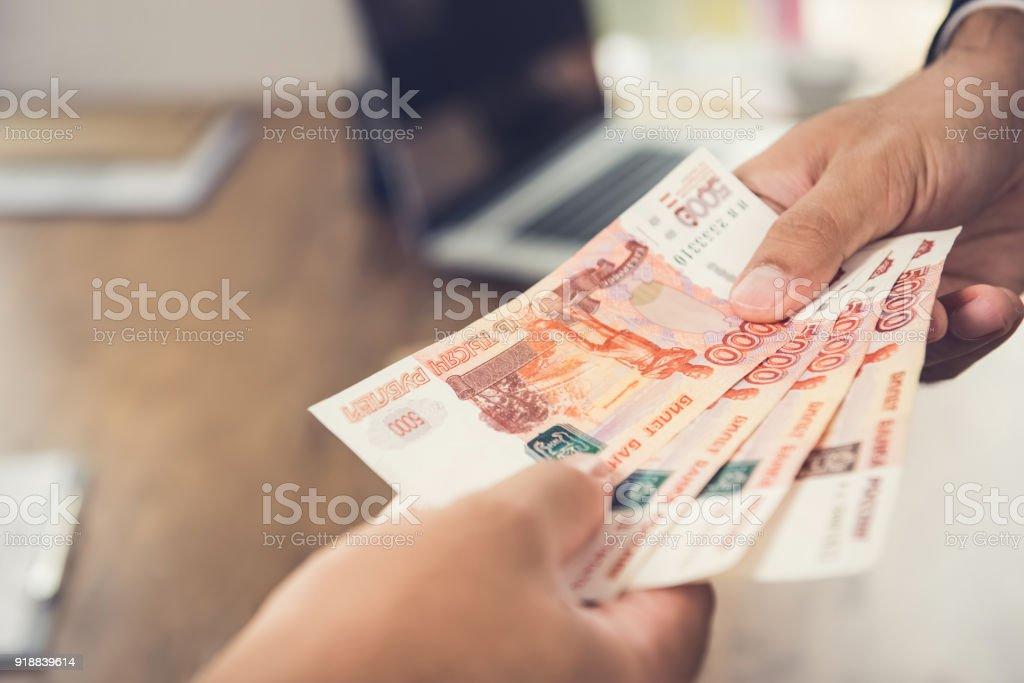 Mano de hombre de negocios dando dinero, divisa Rublo Ruso (RUB), a su pareja - foto de stock