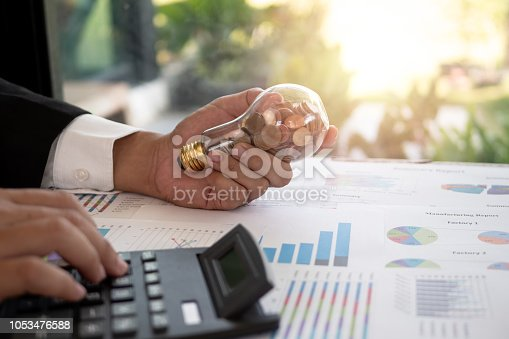 Hand of businessman hold light bulb with coin. Concept of Cost reduction and Reduce energy