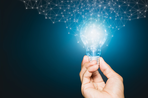 Hand of businessman holding illuminated light bulb, New ideas, innovation and inspiration concepts.