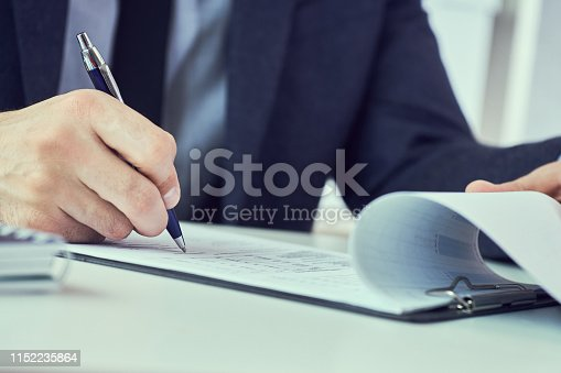 Businessman signing document at table in white office close-up.