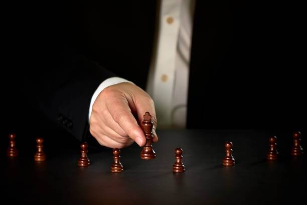 hand of businessman moving chess figure in competition success play stock photo