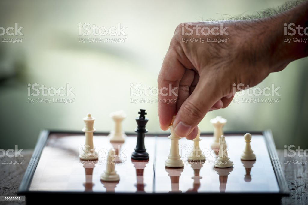 Hand of businessman moving chess on a Board of wood. game, strategy, management or leadership, business success and teamwork concept stock photo