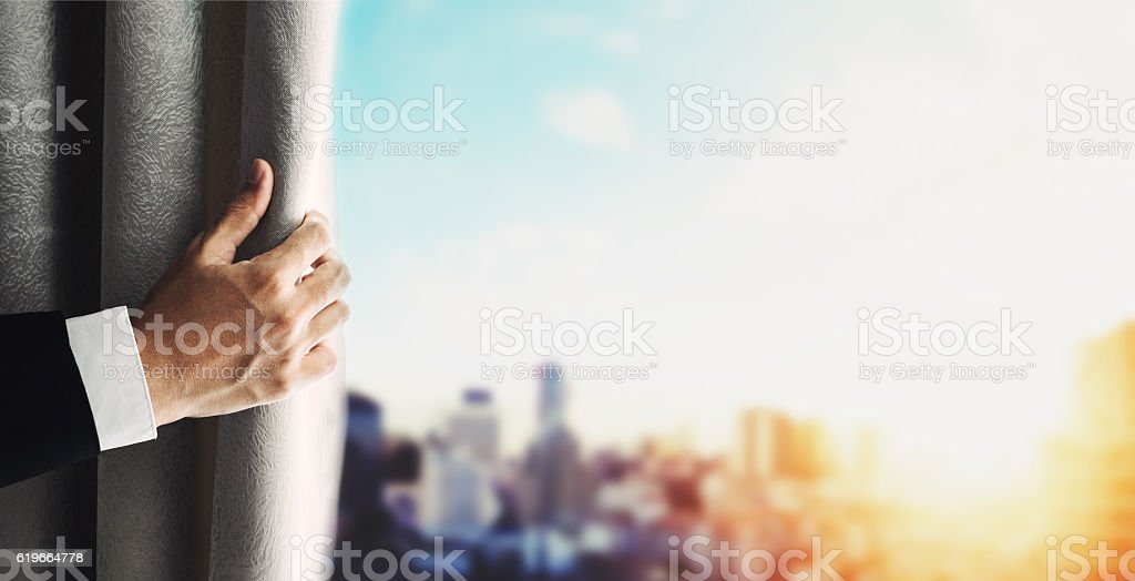 Hand of businessman opening curtain with blurred defocus panoramic cityscape stock photo