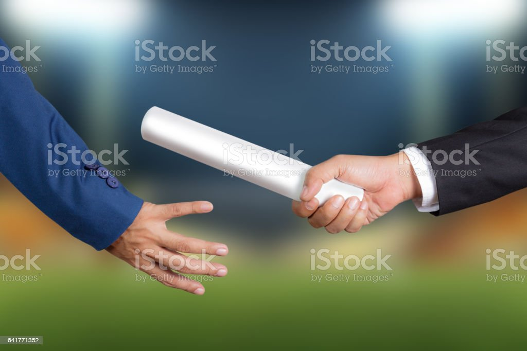 Hand of businessman passing relay baton to colleague stock photo