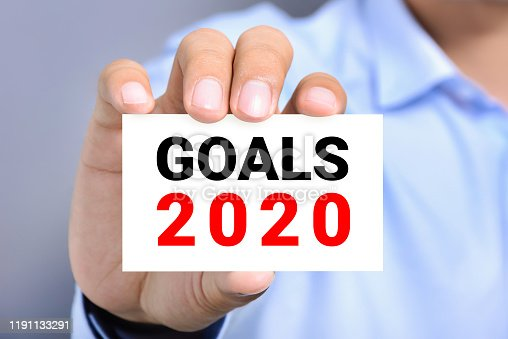 Hand of businessman showing card with text GOALS 2020