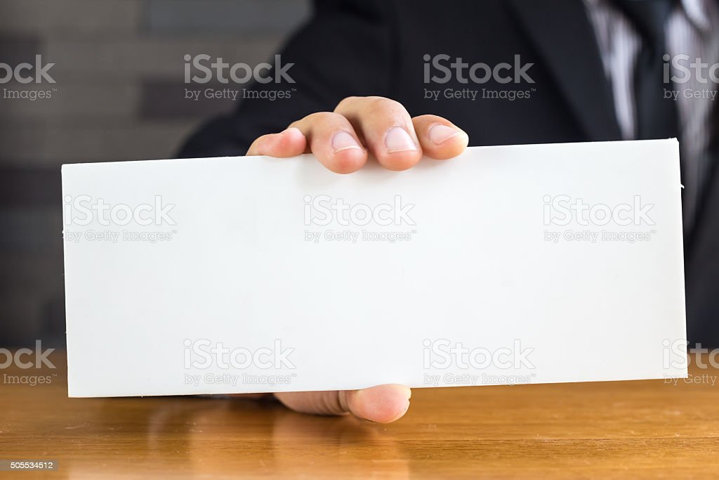 Hand of businessman showing white paper stock photo