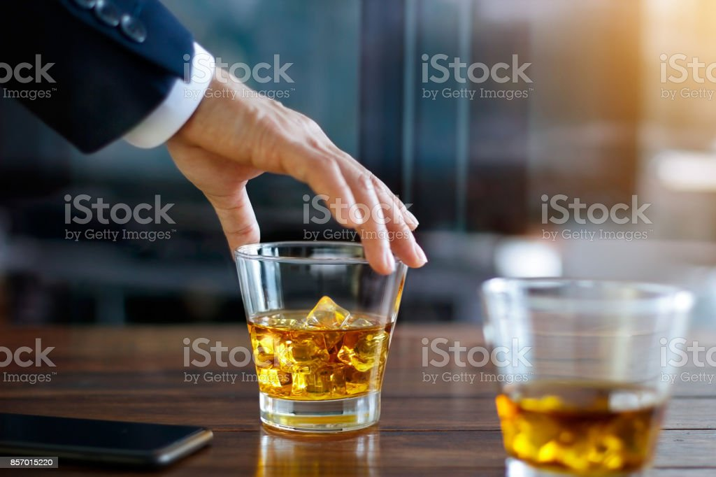 Hand of businessman touching glass of bourbon whiskey in building background stock photo