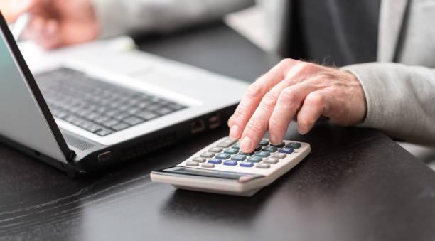 Hand of businessman using calculator stock photo