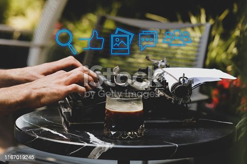 1125093513 istock photo Hand of businessman using typewriter with icon social media and social network. Online marketing concept 1167019245