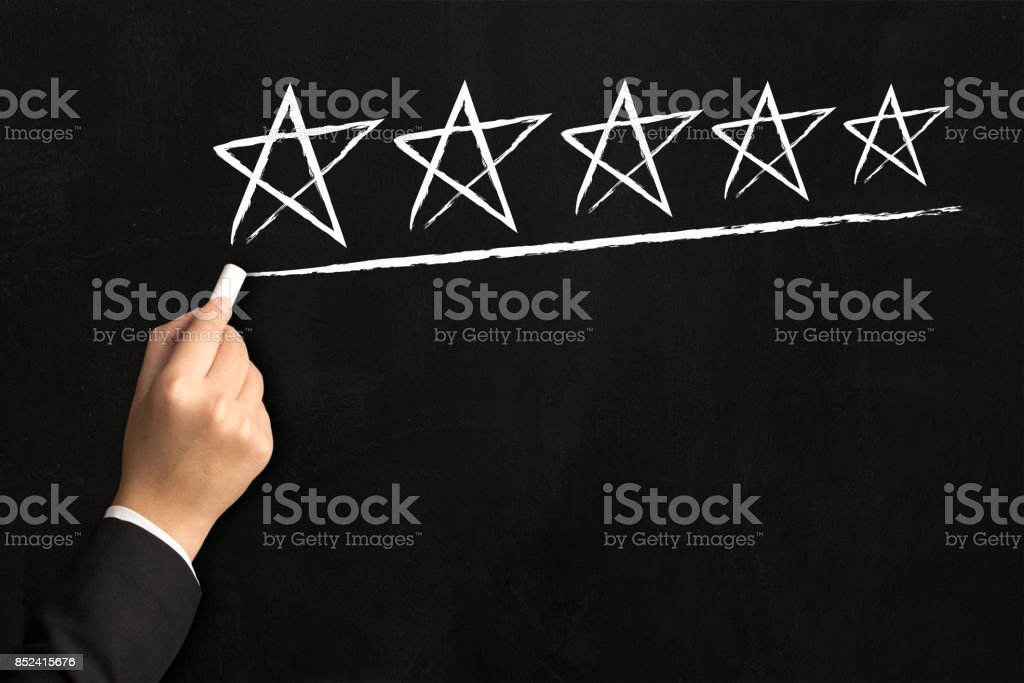 Hand of businessman writing five star on black board, Business increase rating of company concept stock photo