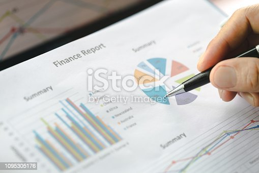 istock Hand of businessman writing on paper in office, graphs showing the results of their successful teamwork, 1095305176