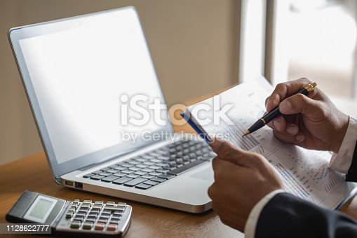 801895196istockphoto Hand of businessman writing on paper in office, graphs showing the results of their successful teamwork, 1128622777