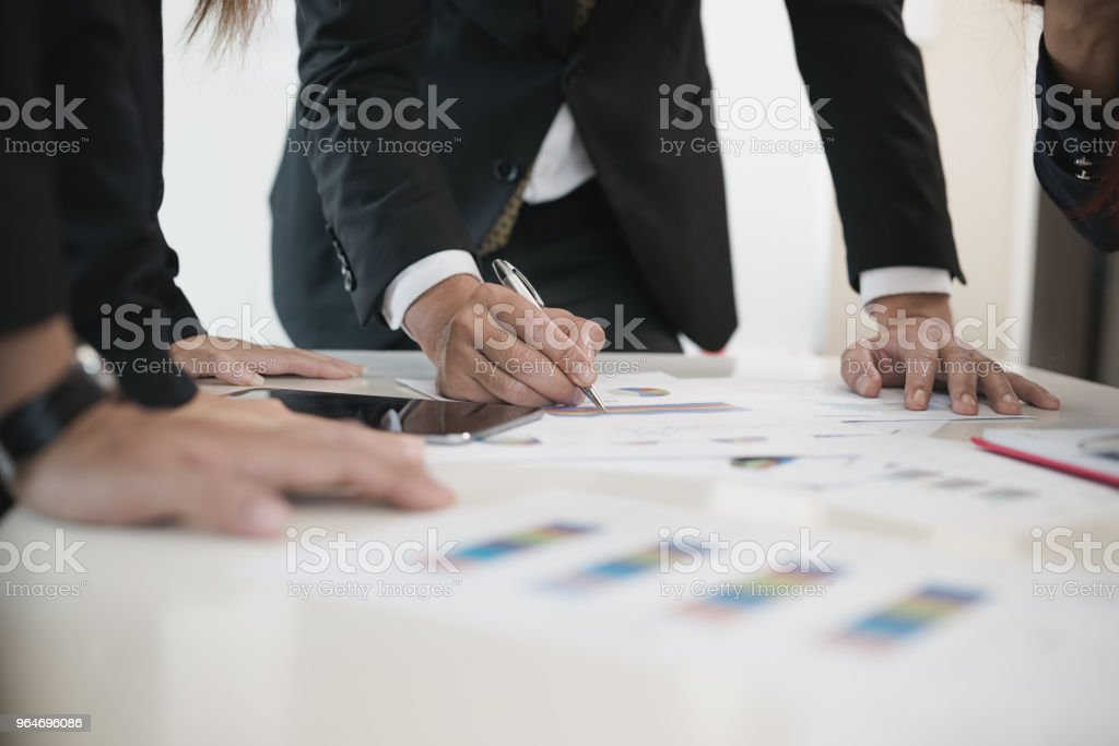 Hand of businessmen write business document charts at office desk. Group of people  are business analyzing. brainstorming, teamwork, meeting concept. royalty-free stock photo