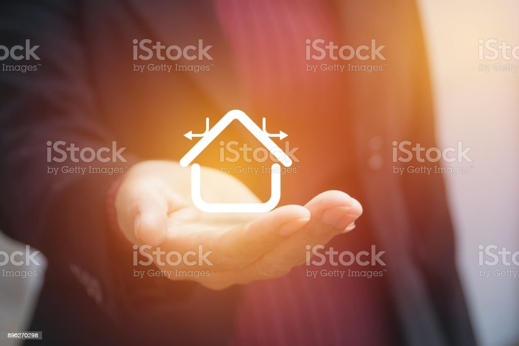 Hand of businesswoman holding house icon concept stock photo