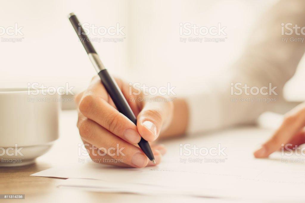 Hand der Geschäftsfrau schreiben auf Papier im Büro – Foto