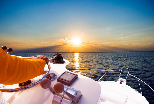 Hand of captain on steering wheel of motor boat in the blue ocean during the fishery day. Success fishing concept. Ocean yacht stock photo