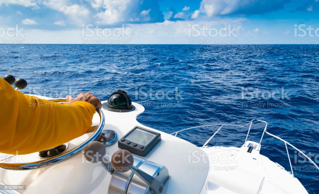 Hand of captain on steering wheel of motor boat in the blue ocean stock photo
