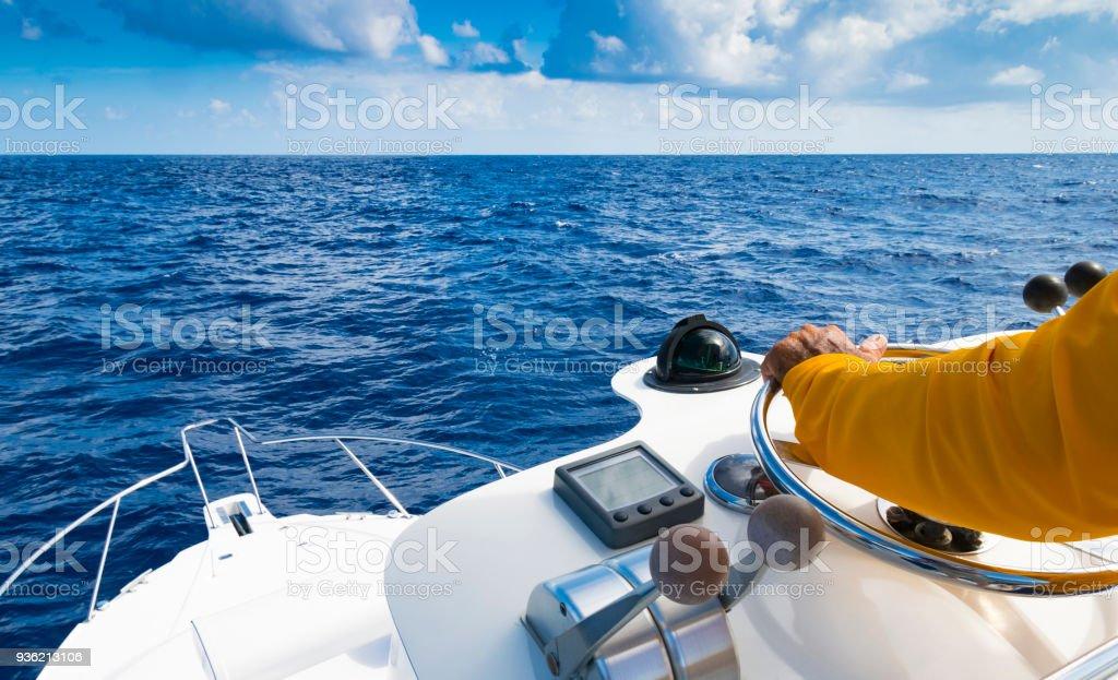 Hand des Kapitäns auf Lenkrad Motorbootes im blauen Ozean tagsüber Fischerei. Angeln-Erfolgskonzept. Ocean-yacht – Foto