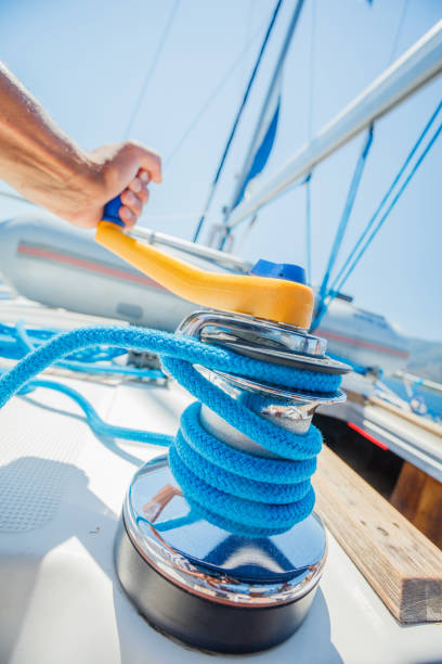 Hand of captain sail boat working on the boat with Winch on a sailboat. Yacht tackle during the ocean voyage, sailing concept. Outdoors horizontal colored closeup image stock photo