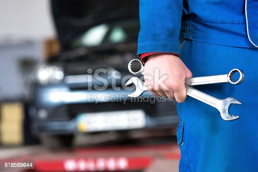 istock Hand of car mechanic with wrench. Auto repair garage. 518589644