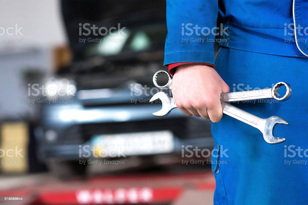 Hand of car mechanic with wrench. Auto repair garage. stock photo