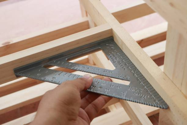 Hand of carpenter is measuring angle of wooden furniture stock photo