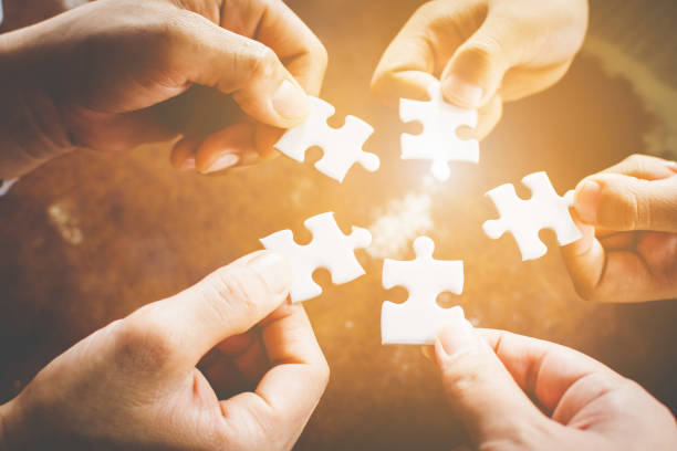 hand of diverse people connecting jigsaw puzzle. concept of partnership and teamwork in business - changing form stock pictures, royalty-free photos & images