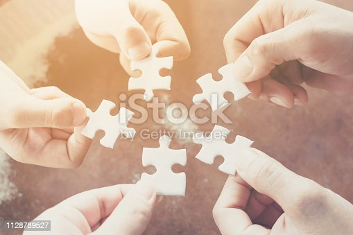 istock Hand of diverse people connecting jigsaw puzzle. Concept of partnership and teamwork in business 1128789527