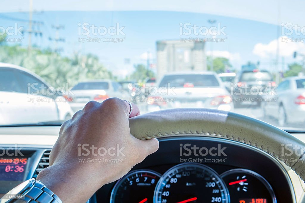 Hand of driver holding steering wheel, with traffic view stock photo