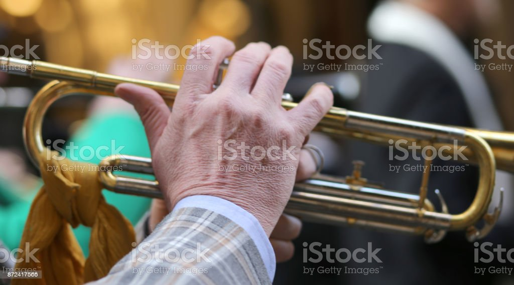 hand of elderly man playing the trumpet in the music band stock photo