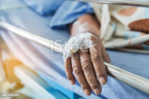 Close up hand of elderly patient with intravenous catheter for injection plug in hand during lying in the hospital bed