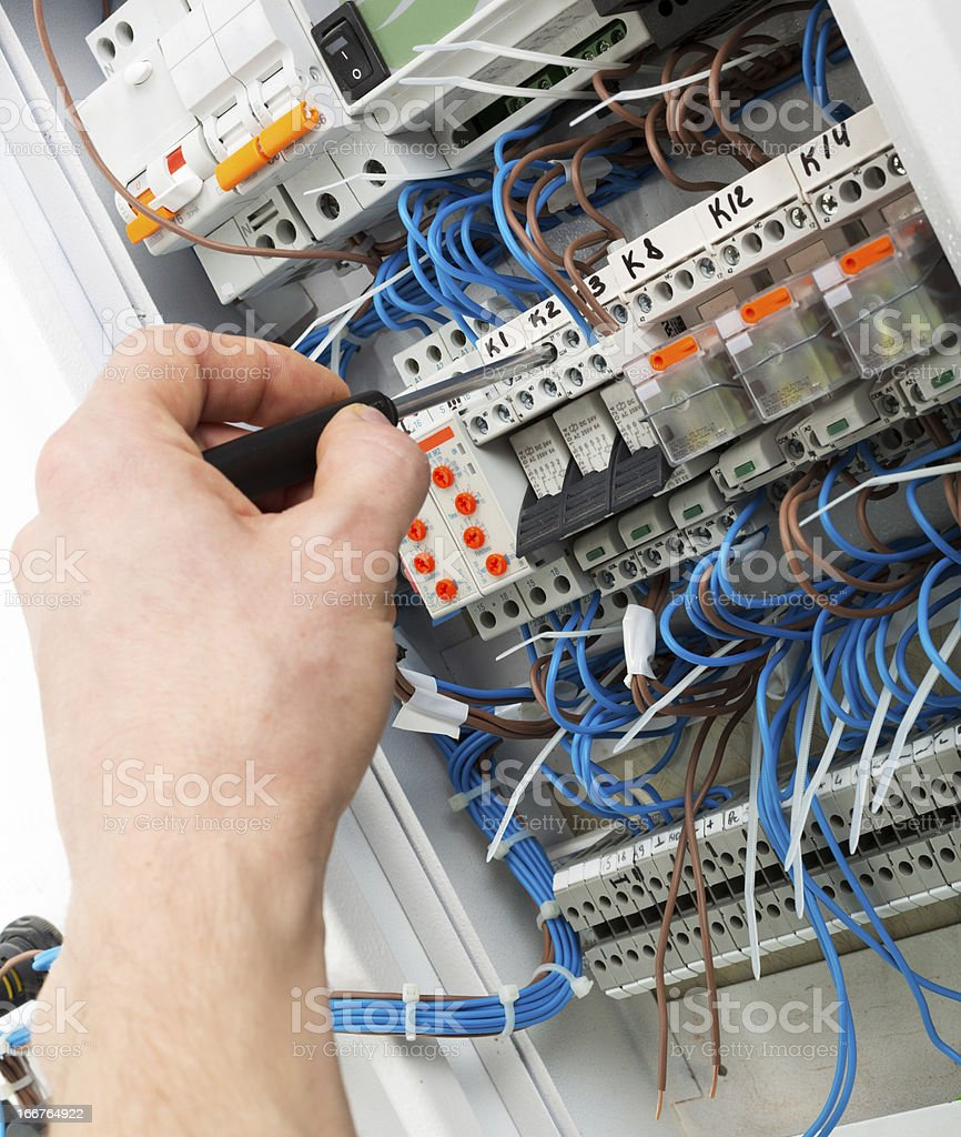 Hand of electrician in fuse box stock photo