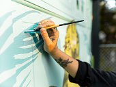 Close up of hand of Female mural artist creating art on the garage door of the private home in the city.