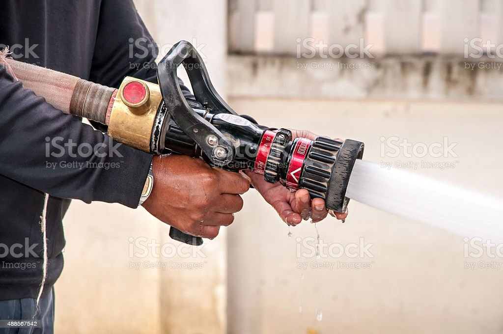 Hand of Firefighter at works with water cannon stock photo
