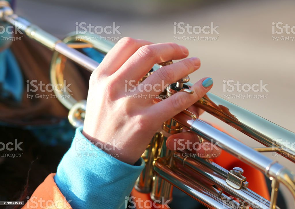 hand of girl playing the trumpet in the music band stock photo
